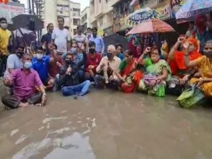 Citizens' agitation sitting in stagnant water due to negligence by the administration ... | रस्ते दुरुस्ती आणि नाले सफाईच्या मागणीसाठी साचलेल्या पाण्यात बसून नागरिकांचं आंदोलन