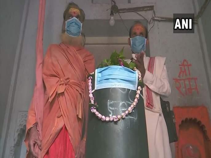 unique protest in varanasi against air pollution | मोदींच्या वाराणसीत प्रदूषण वाढलं; देवालाही मास्क लावलं