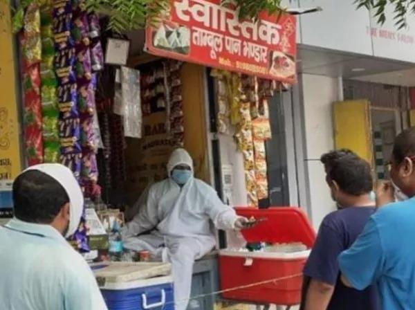 CoronaVirus Marathi News meet paan seller wearing ppe kit selling paan banaras | CoronaVirus News : कोरोनाचा धसका! पीपीई किट परिधान करून पानवाला चालवतोय टपरी