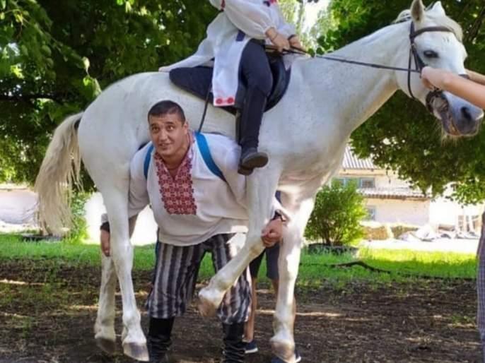 Man lifts the horse on the shoulder and lifts 152 kg with one hand see shocking video | Man lifts the horse on the shoulder : बाप रे बाप! घोड्याला एका खांद्यावर उचलून धाव धाव धावतोय पठ्ठ्या; समोर आला Shocking Video