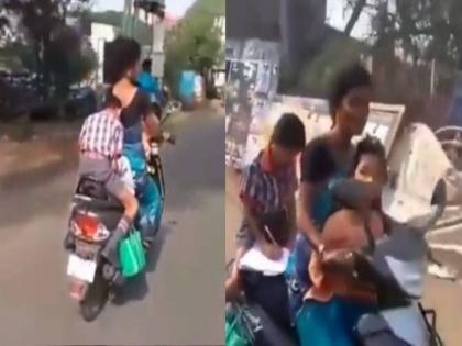 viral video of a child doing homework on moving scooty putting life in danger | चलती स्कूटी पर होमवर्क पूरा करते बच्चे का वीडियो हुआ वायरल, लोगों ने कहा- महान लोग आखिर मिनट में अपना काम करते हैं