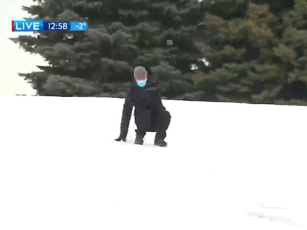viral video: Journalist slides downhill during weather report | टीवी पर मौसम की लाइव रिपोर्टिंग के दौरान बर्फ से फिसलकर बाल-बाल बचे पत्रकार, देखें वीडियो